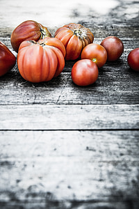 red tomatoes on wooden surface