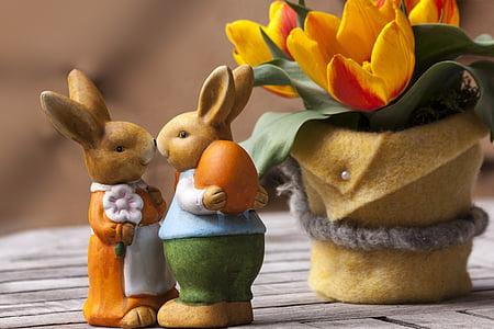 two brown rabbit figurines near yellow tulips flower centerpiece
