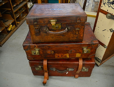 three stacked brown suitcases