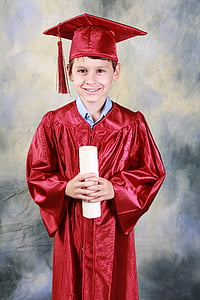 smiling boy wearing red academic dress holding diploma