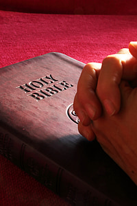 person's hands on Holy Bible
