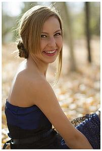 smiling woman wearing blue strapless shirt