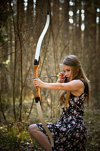 woman in black floral dress holding bow and arrow kneeling in forest