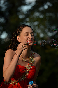 woman in red dress blowing bubbles
