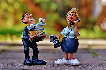 man holding books and woman using telephone figurines