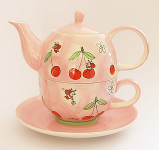 pink and red ceramic kettle on top of pink saucer