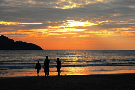 silhouette of three people near in the beach