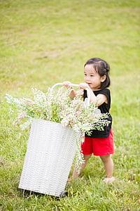 girl wearing black sleeveless shirt holding basket of flowers