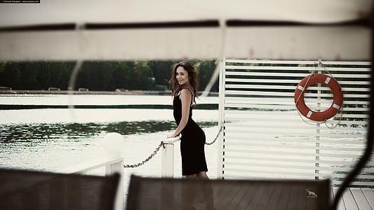 woman wearing black sleeveless dress near body of water