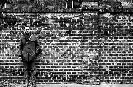 man leaning on bricked wall