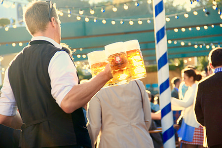 man holding beer mugs filled with beers