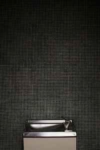gray drinking fountain behind gray wall