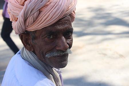 man wearing white top and pink headdress