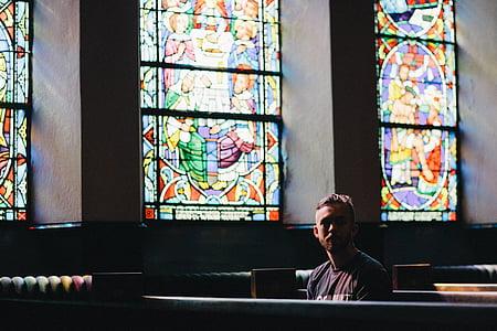 man in maroon crew-neck shirt sitting on pew inside church