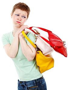 woman carrying three leather handbags