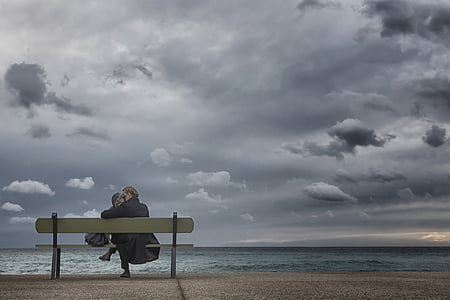 woman sitting on bench facing body of water under cloudy sky