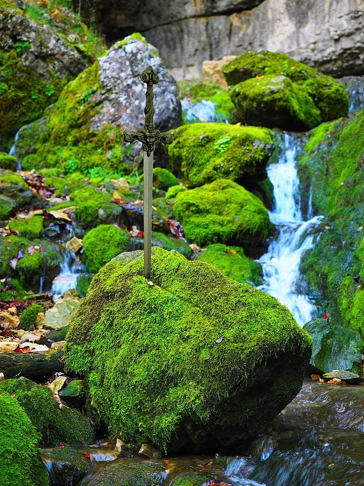 sword on moss-covered rock boulder