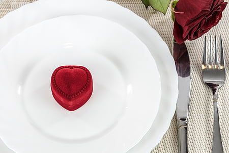 heart-shaped red suede ring box on round white plate