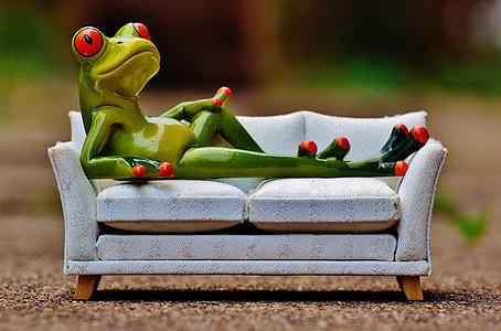 green tree frog lounging on white sofa figurine