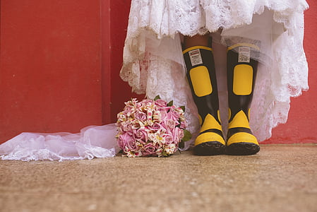 person wearing black-and-yellow rain boots beside flower bouquet