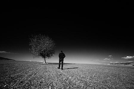 grayscale photography of man wearing jacket near tree
