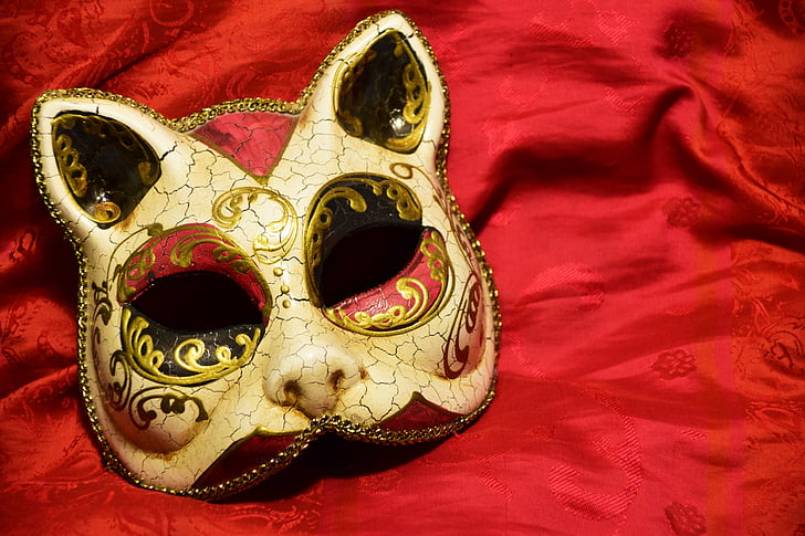 gold masquerade cat mask on red textile