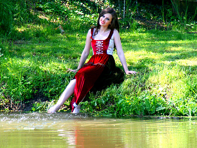 woman sitting on grass in front of body of water
