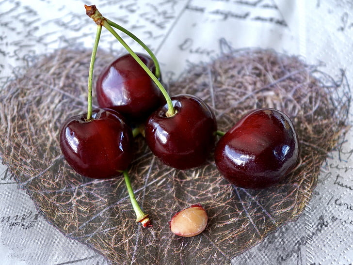 four red cherries on heart brown textile