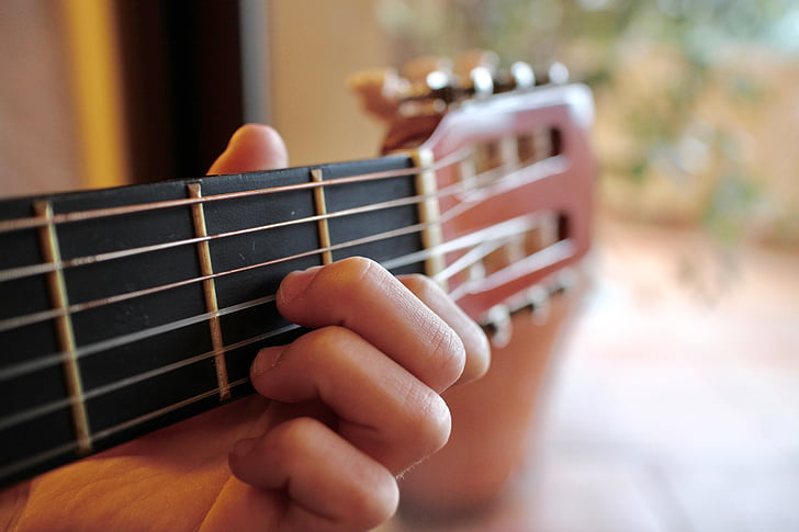 Royalty-Free photo: Person holding brown classical guitar | PickPik