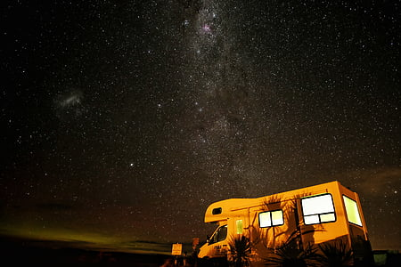 brown recreational vehicle parked near plants during nighttime