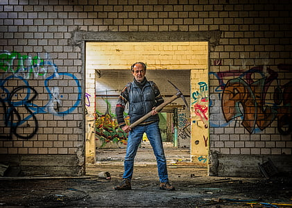 man wearing black vest and blue jeans holding pickaxe behind wall with graffiti
