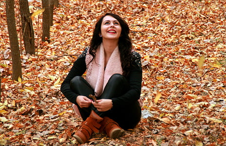 woman in black long-sleeved top and black pants sitting on brown leaves