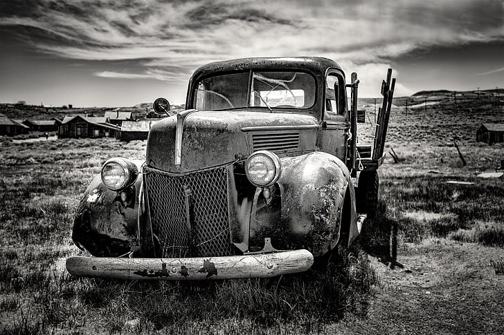 grayscale photo of single cab pickup truck on grass field