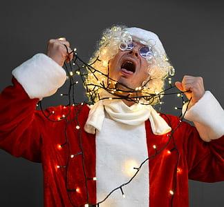 man in white Santa Claus costume choking himself using string lights