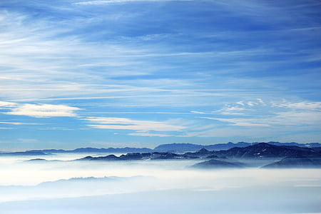 mountain range above clouds during daytime