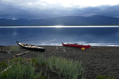 two red and black canoes on seashore