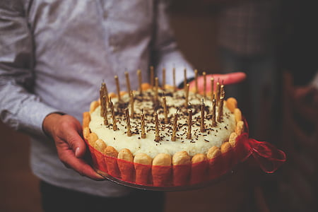 man holding cake with candles