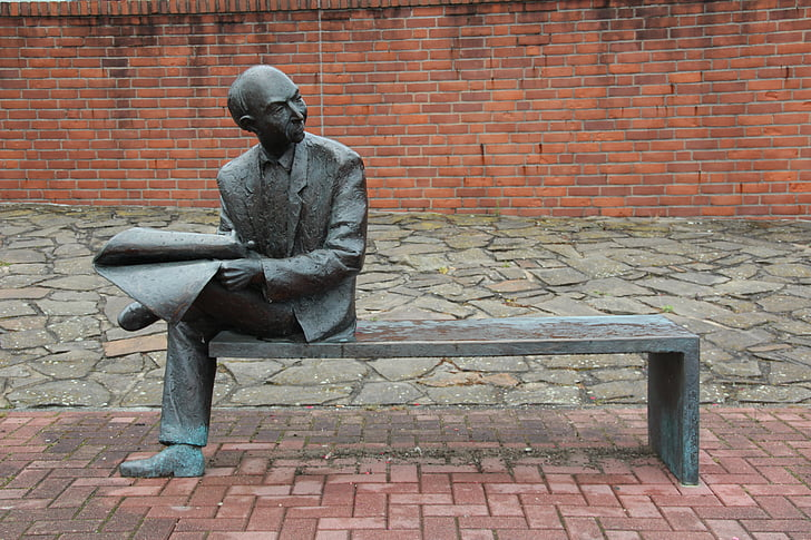 man sitting on bench holding paper statue