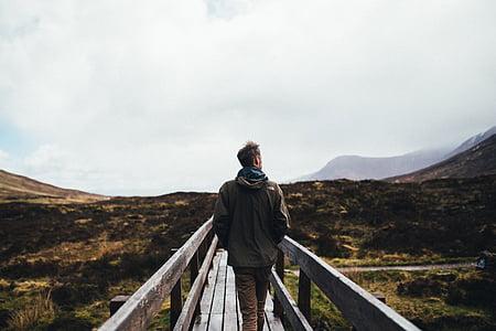 man standing on wooden bridge near mountain range