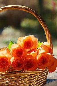 close up photo of basket of orange roses