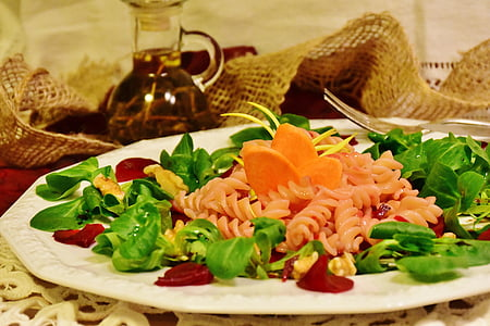 pasta with carrots, vegetable salad and bacon on round white plate