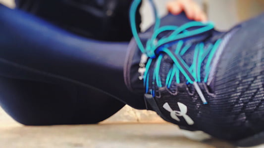 person wearing black leggings and black Under Armour running shoe