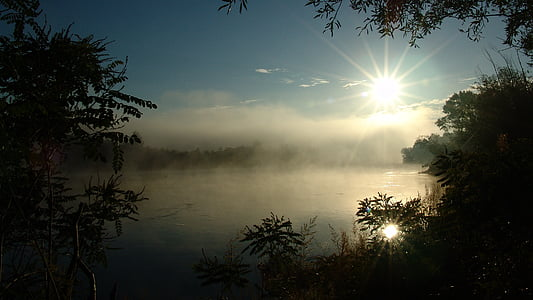 body of water with fog during sunrise
