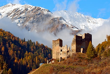 beige concrete ruins surrounded with tall trees near snow capped mountain at daytime