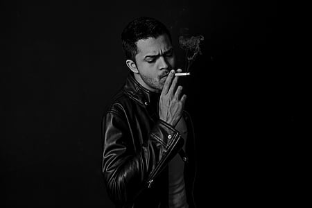 grayscale photography of man wearing black leather jacket holding cigarette stick