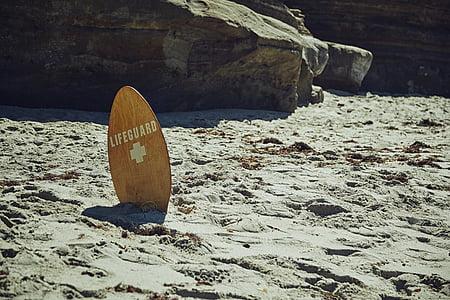 brown Lifeguard skimboard on gray sand