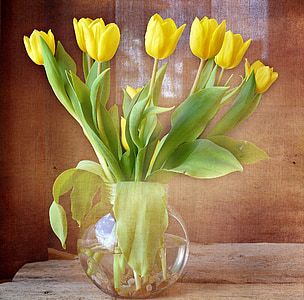 yellow tulip flowers in clear glass vase centerpiece