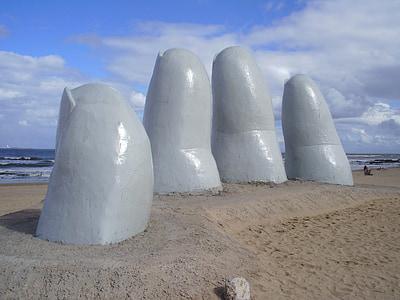 hand monument near beach at daytime