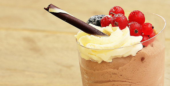 glass of chocolate shake with cherries and wafer stick