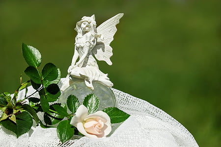 white fairy figurine on white cloth next to white rose